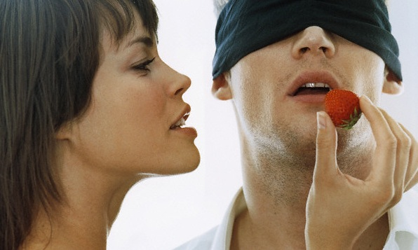 Young Woman Feeding Strawberry to Blindfolded Man